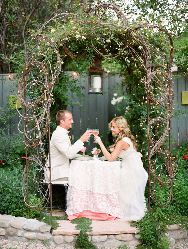 a fairy tale woodland wedding arch of branches and vines, with greenery, neutral bloomsand leaves is romantic