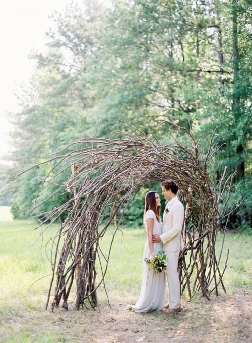 a cool bent wedding arch of only branches is a bold natural statement, totally out of the box