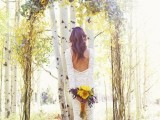 a rustic woodland wedding arch of branches and twigs, with pale foliage and sunflowers on top is lovely and bright