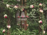 a bright woodland wedding arch of branches and twigs, with greenery and leaves, white and bright pink blooms and moss at the base