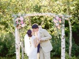 a rustic woodland wedding arch of birch branches, pale greenery, white and pink blooms is a simple and stylish idea with a rustic feel