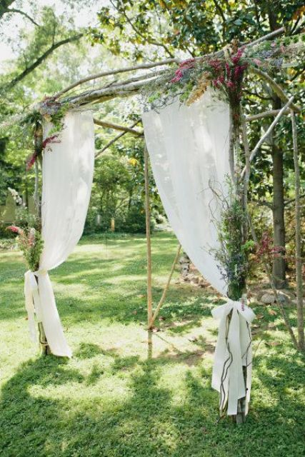 a wild woodland wedding arch of branches and sticks, with wildflowers, white curtains and bows is an amazing idea for a woodland wedding