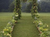 a cool woodland wedding arch fully covered with greenery and bold yellow blooms and with a forest view is fantastic