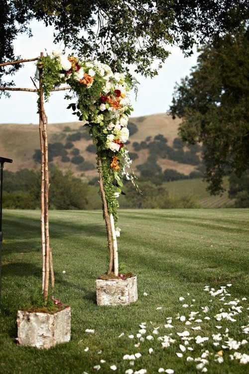 a rustic woodland wedding arch of branches, with greenery and bright blooms and planters wrapped with bark