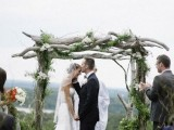 a wild woodland wedding arch of branches, with greenery and white blooms and a cool view of the valley