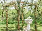 a romantic woodland wedding arch of branches and twigs, with greenery and pastel blooms and petals inside for a spring or summer wedding