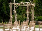 a rough branch wedding arch with greenery and pastel blooms is a cool idea for a woodland wedding