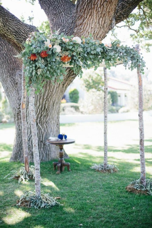 a woodland wedding arch of branches, with greenery, pastel and bold blooms and greenery at the base