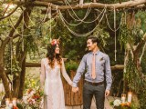 a woodland wedding arch of real trees and branches, with yarn and tassels, with candles and bright blooms around is a very natural idea