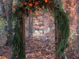 a gorgeous bright wedding arch of wood covered with evergreens and ferns, with bright blooms and moss on top is amazing for a fall woodland wedding