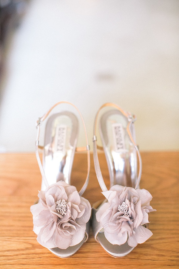 silver wedding shoes with lavender colored fabric flowers on top are perfect for a summer garden bride