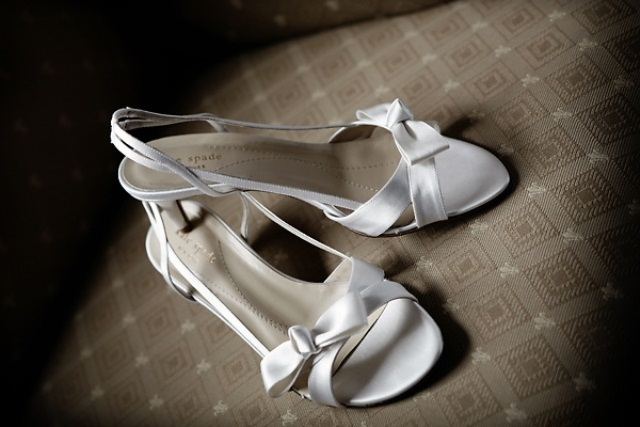 simple white strappy heeled sandals with small bows are a nice and trendy idea for a summer bride
