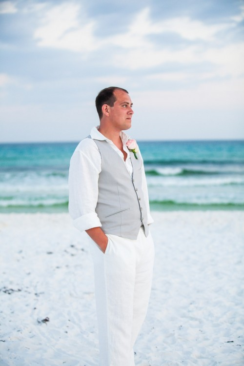 white pants, a white shirt, a light grey vest and a floral boutonniere for a relaxed beach outfit