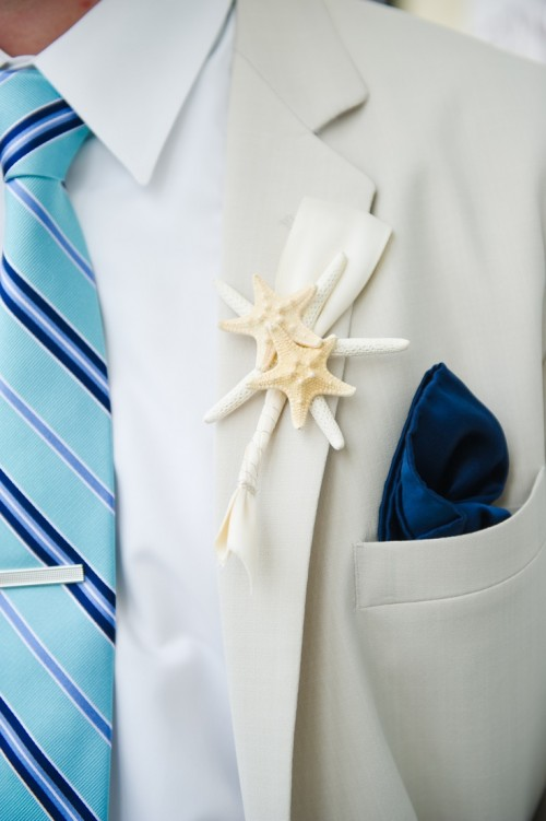 a creamy suit, a bold blue striped tie, a navy handkerchief and a starfish boutonniere for a more formal look