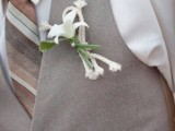 an ivory shirt, a striped tie, a light grey waistcoat and a beachy boutonniere won't make you feel too hot