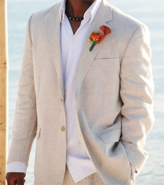 a tan linen suit, a white shirt, a bright floral boutonniere for a not too formal look