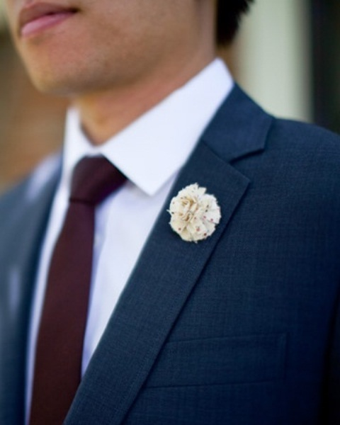 a formal groom's outfit with a navy suit, a white shirt and a plum-colored tie
