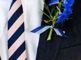 a black suit, a white shirt, a striped tie and a bright floral boutonniere to stand out with colors