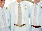 light blue thin stripe suits, white shirts, striped ties, neutral flower boutonniere to give a nod to the sea theme
