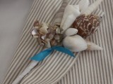 a thin striped suit, a white shirt and a seashell boutonniere for a dapper beach look