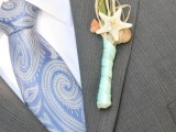 a light grey suit, a blue printed tie and a colorful boutonniere
