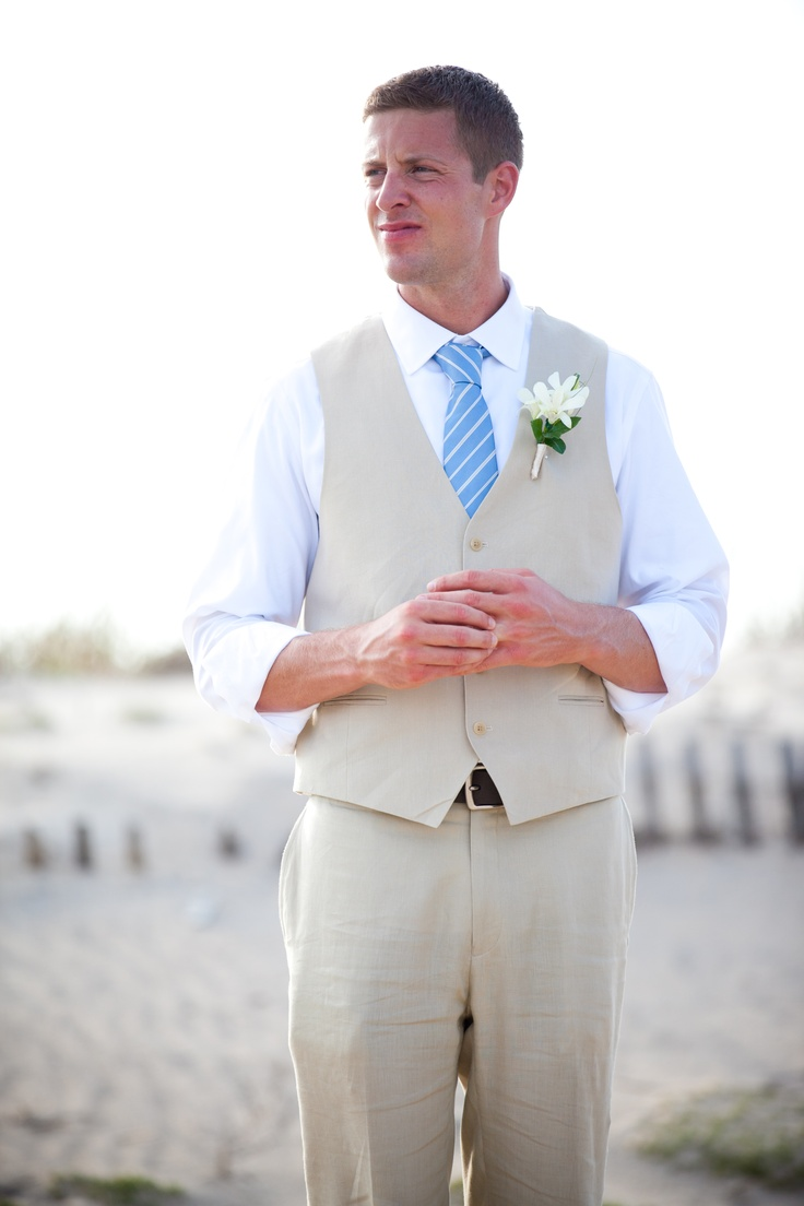 a neutral suit with a waistcoat, a white shirt and a blue striped tie is a nice combo for a beach groom