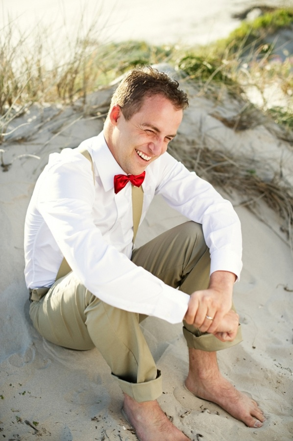 tan pants, tan suspenders, a white shirt and a red bow is a chic and bright beach groom look