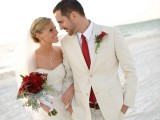 a creamy suit, a white shirt, a red tie and a red floral boutonniere for a neutral yet color-accented look