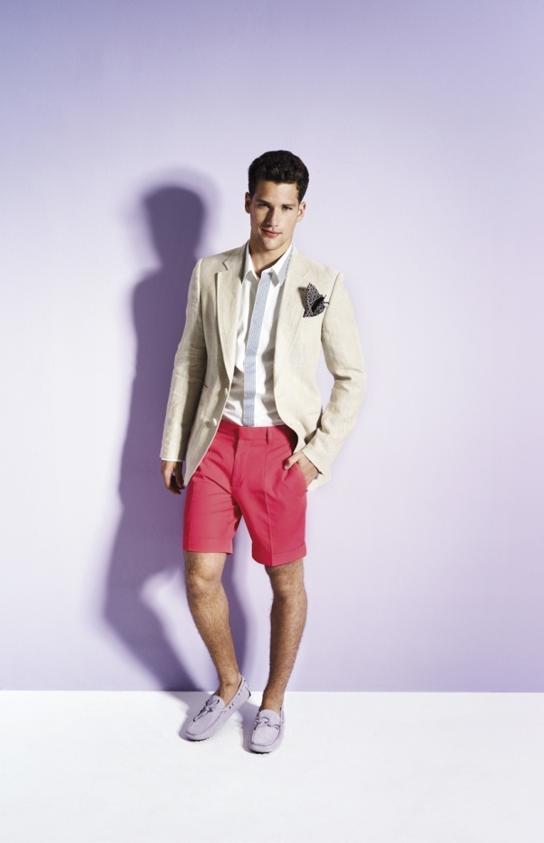 a bold and non traditional look with coral shorts, grey moccasins, a creamy jacket, a striped shirt