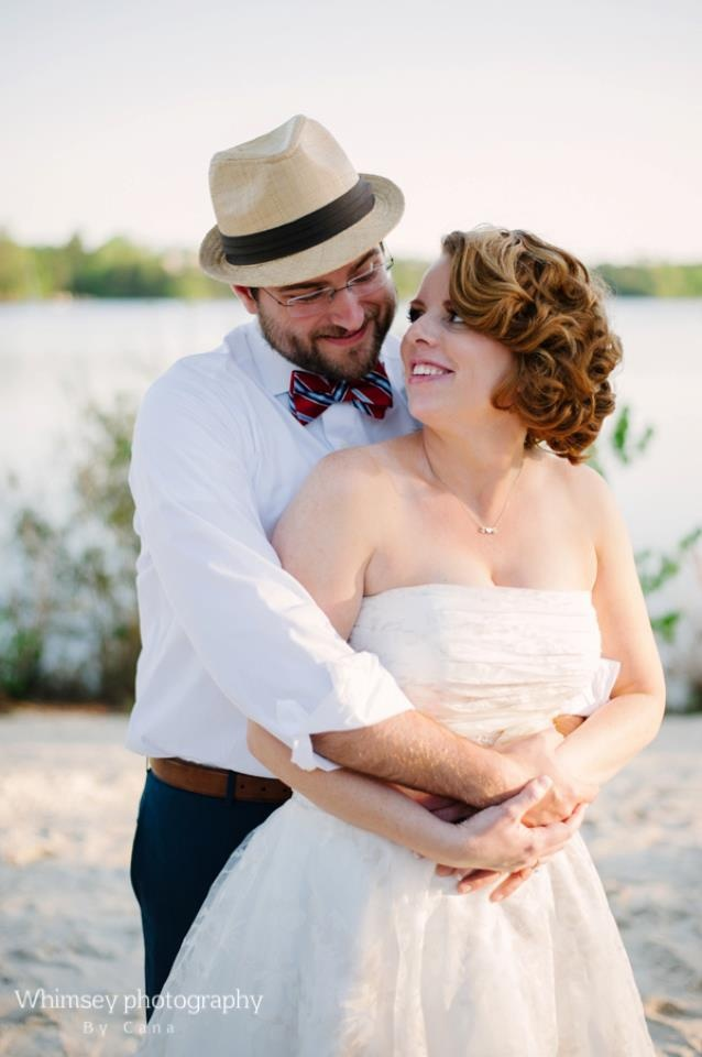 navy pants, a white shirt, a colorful striped tie and a hat for a dapper beach groom's outfit