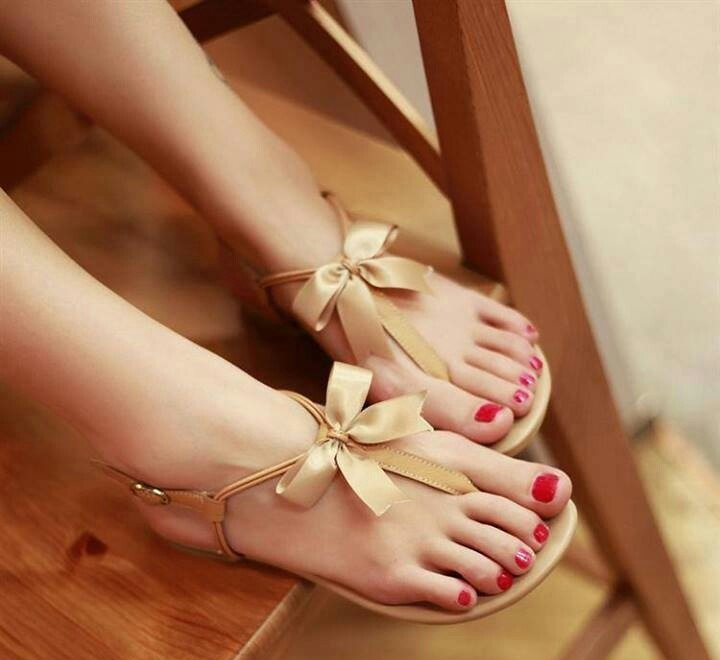 cool flat tan colored sandals with bows are amazing for a beach bride and can be worn after the wedding, too