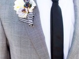 a vintage-inspired groom's look with a grey suit, a black tie, a white button down and a floral boutonniere