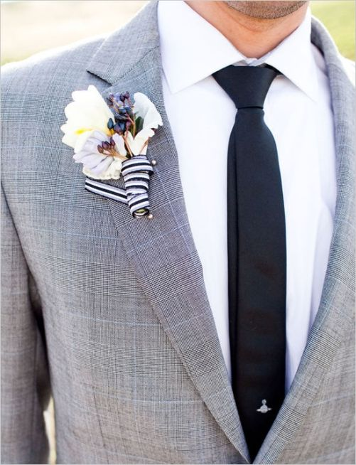 a vintage inspired groom's look with a grey suit, a black tie, a white button down and a floral boutonniere