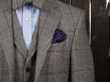 a grey tweed three-piece suit with a matching bow tie and a blue shirt plus a navy handkerchief