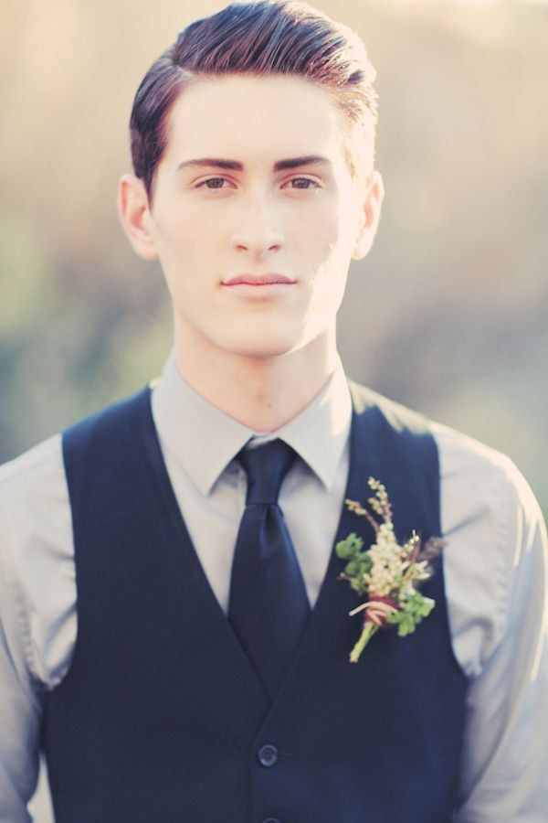 a chic groom's look with a grey button down, a navy tie and waistcoat plus a floral boutonniere