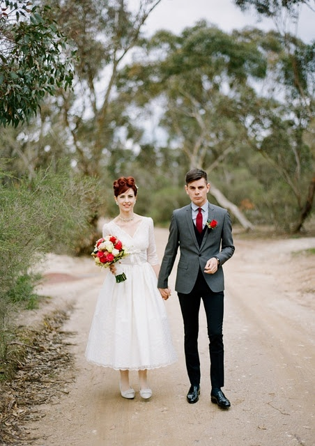 an elegant vintage groom's look with black pants and a wiastcoat, a grey blazer, a blue shirt and a red tie