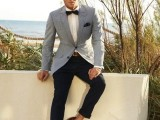 a catchy nautical groom's look with black pants, a white button down, a black bow tie, a blue thin striped blazer and brown loafers