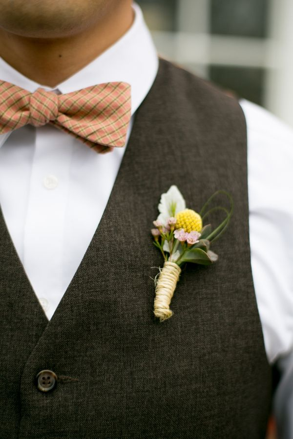 a stylish groom's look with a white button down, a chocolate brown waistcoat and a rust bow tie plus a floral boutonniere