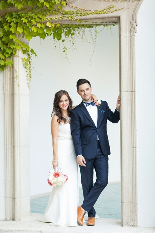 a catchy groom's look with a navy suit, a white button down, amber shoes and a printed bow tie
