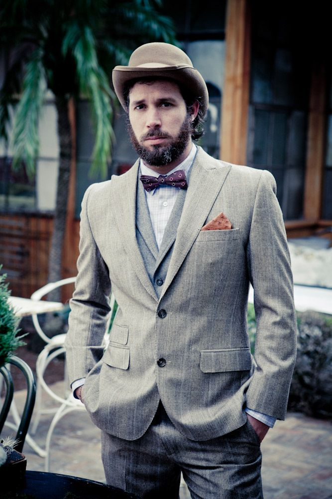 a vintage groom's look with a grey checked suit, a grey waistcoat, a burgundy printed bow tie and a hat