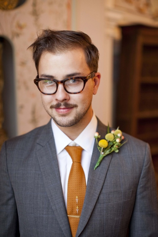 a vintage groom's look with a grey suit, a white button down and a rust tie plus a billy ball boutonniere