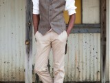 a stylish vintage groom's look with tan pants, a grey waistcoat, a white shirt, a striped tie, a brown cap and amber boots