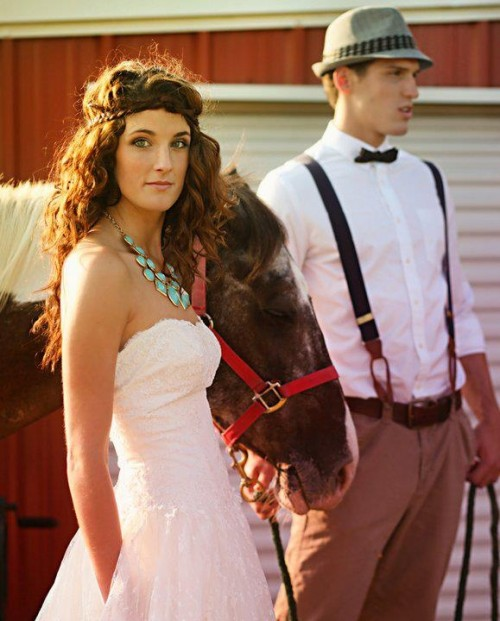 a vintage groom's look with tan pants, a white shirt, black suspenders, a black bow tie and a grey hat