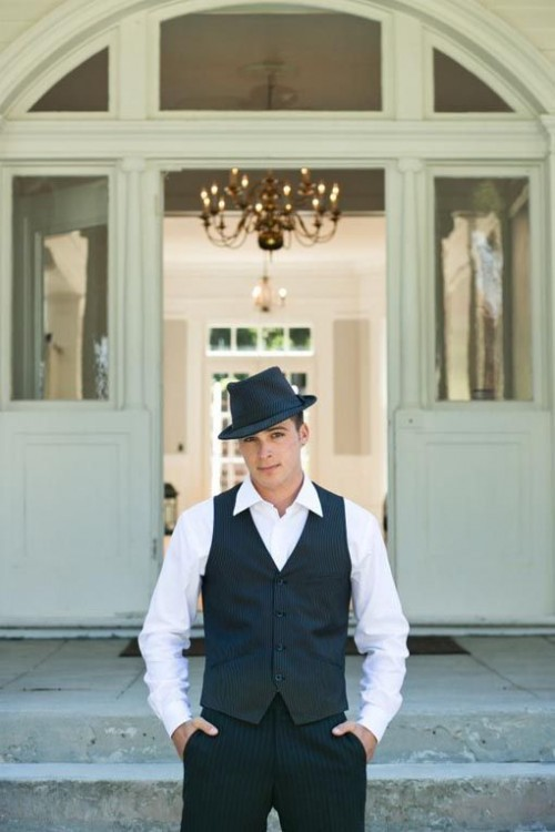 an elegant gangster-styled look with a black thin striped waistcoat and pants, a white button down and a black hat