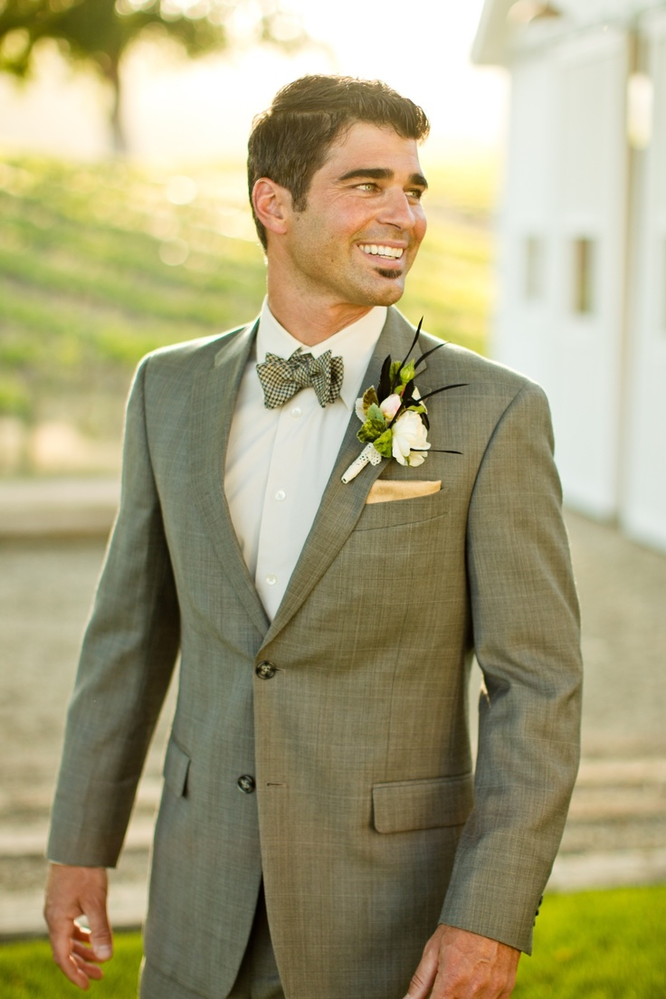 a vintage inspired groom's look with a light grey suit, a white button down and a printed bow tie plus a florla boutonniere