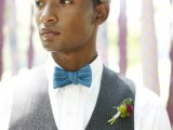 a vintage groom's look with a white button down, a grey waistcoat, a blue bow tie and a cap