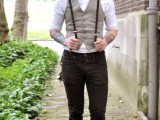 a vintage groom's outfit with black pants, a white shirt, a grey waistcoat, black suspenders and a brown cap