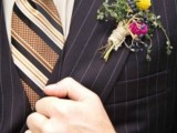 an elegant retro groom's look with a thin striped black three-piece suit, a striped tie and a bright floral boutonniere