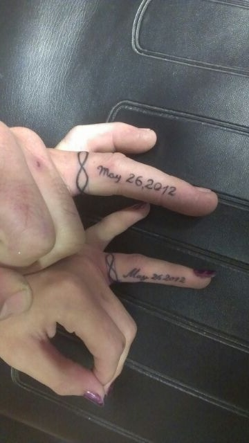 wedding date tattoos done with words and infinity signs put on the sides of the ring fingers