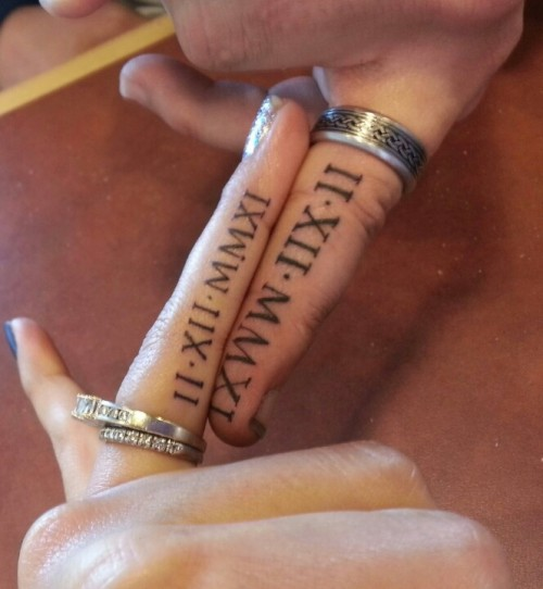 usual wedding bands paired with wedding date tattoos done with roman numbers on the sides of the fingers